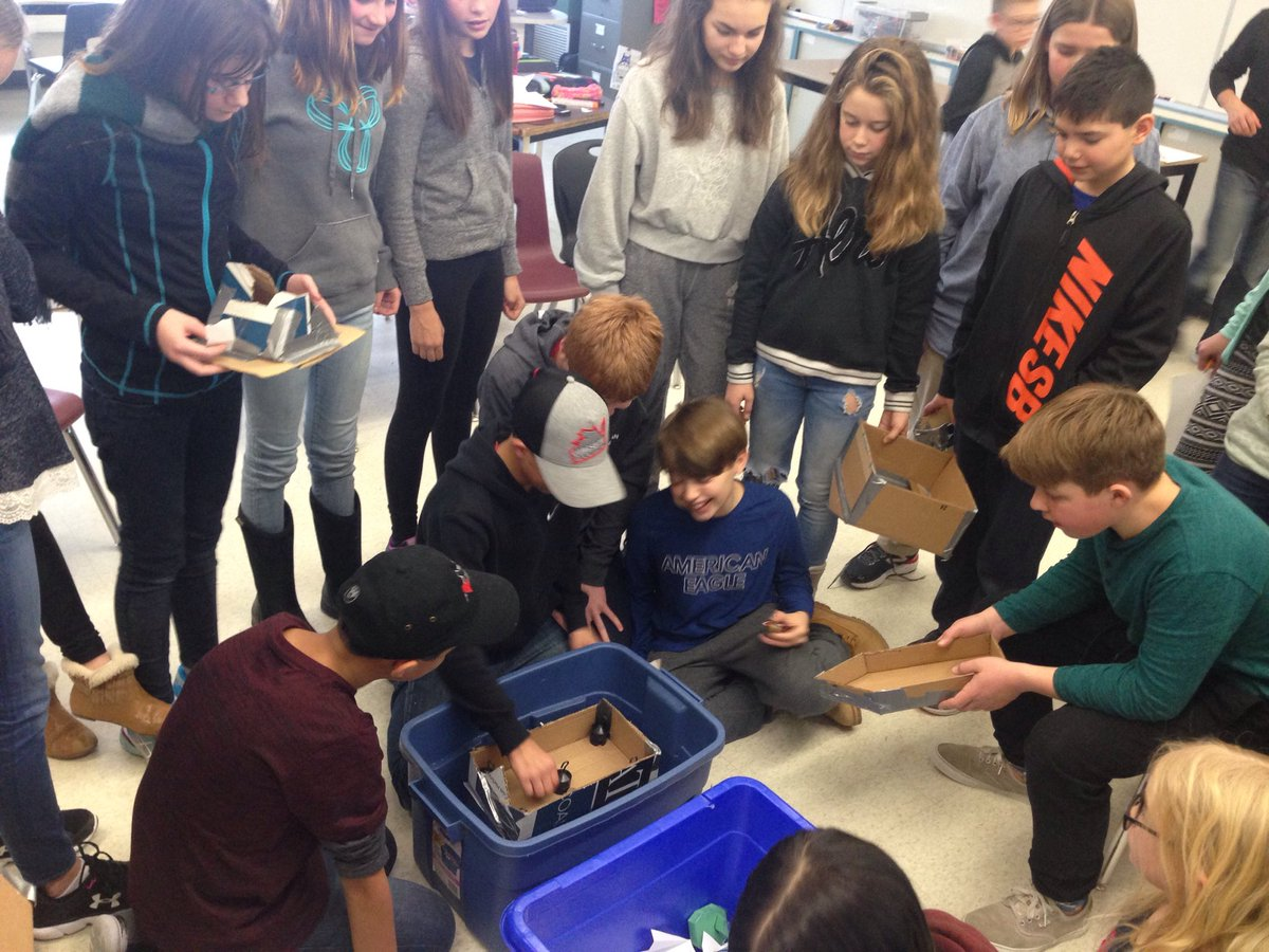 group of students testing a small cardboard boat in a bucket of water