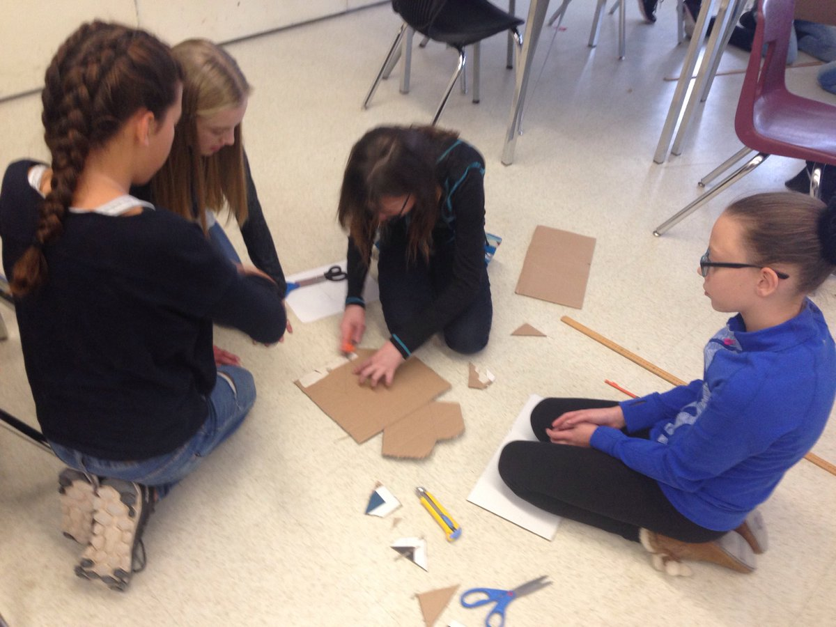 students cutting out cardboard on the floor