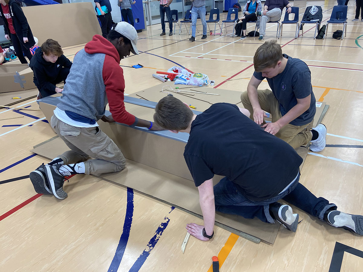 photo of students building the base of their cardboard boat