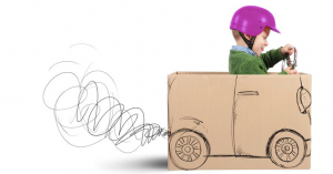Young boy wearing helmet pretending to drive cardboard box as imaginary car