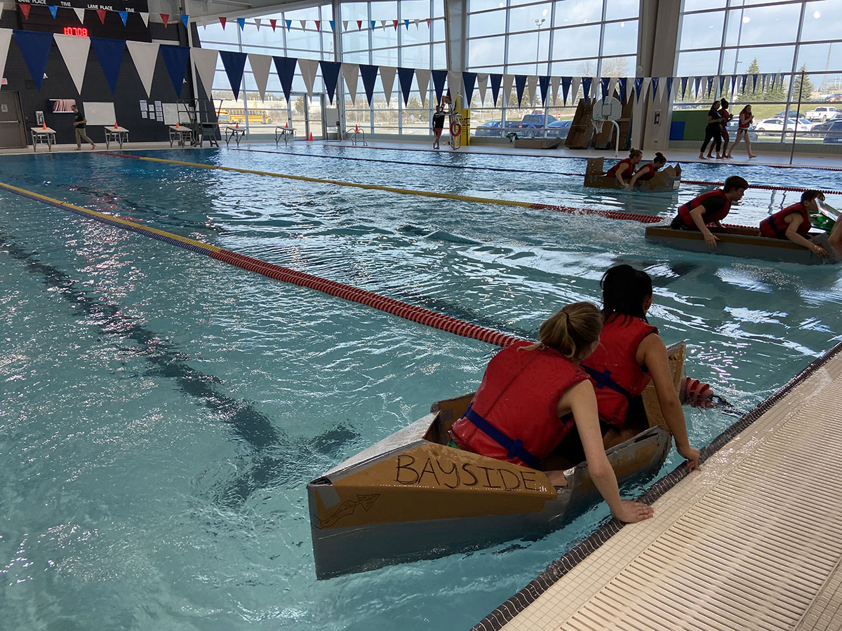 students test their cardboard boats in the water
