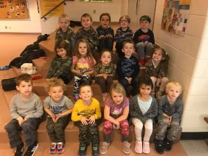 A group of kindergarten students sit together on classroom steps for a class picture